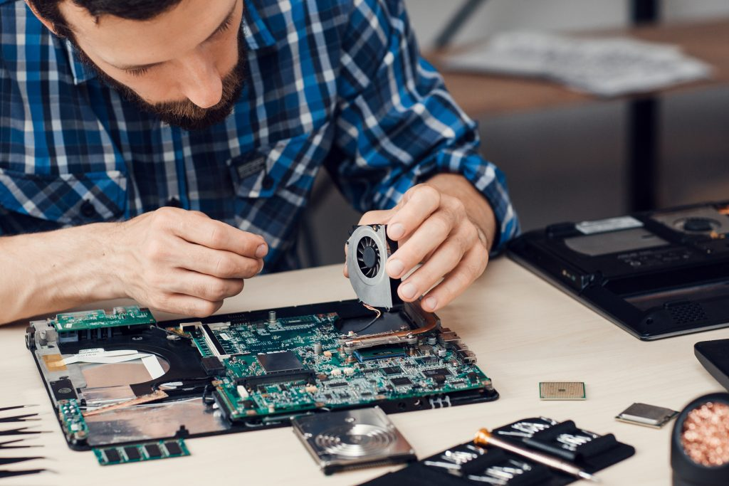 Repairman disassembling laptop motherboard