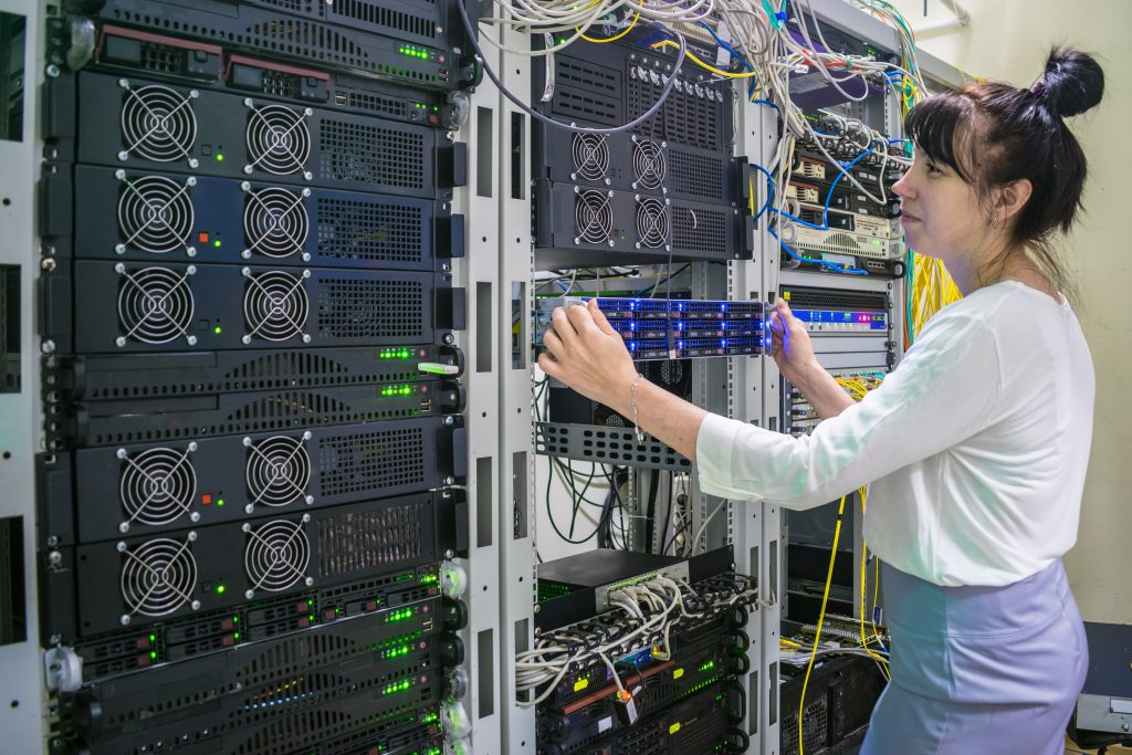 system administrator works with powerful computer equipment. Hosting platform of the Internet provider. A woman installs a new server in a modern data center