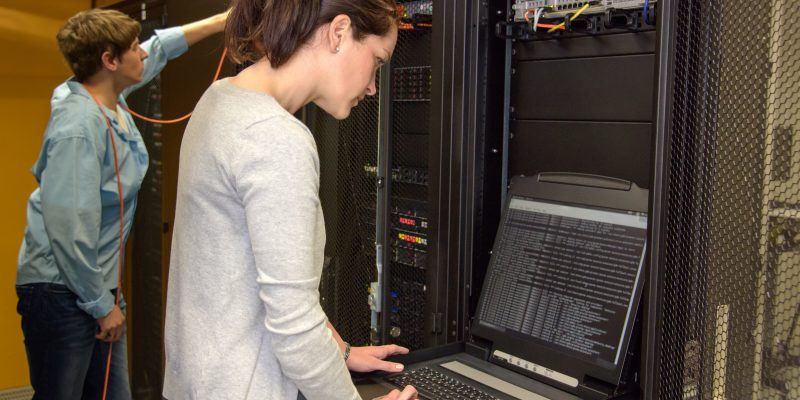 Female technician in server room checking network security with laptop